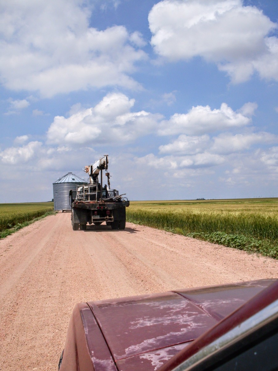 A convoy: First went our friend Les, with the shortened bin on a big trailer. Next came my husband, in the boomtruck, which we used to load and unload the bin. Last, came the kids and I, in the car.