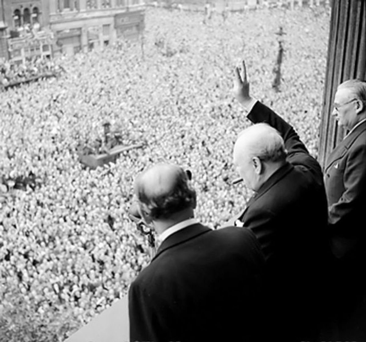 Sir Winston Churchill gives his V for Victory sign to crowds in Whitehall on the day he broadcast to the nation that the war with Germany had been won, 8 May 1945