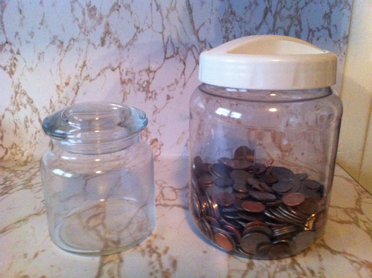 The coins from the jar are moved to the larger container, presenting an opportunity to fill it with more change.
