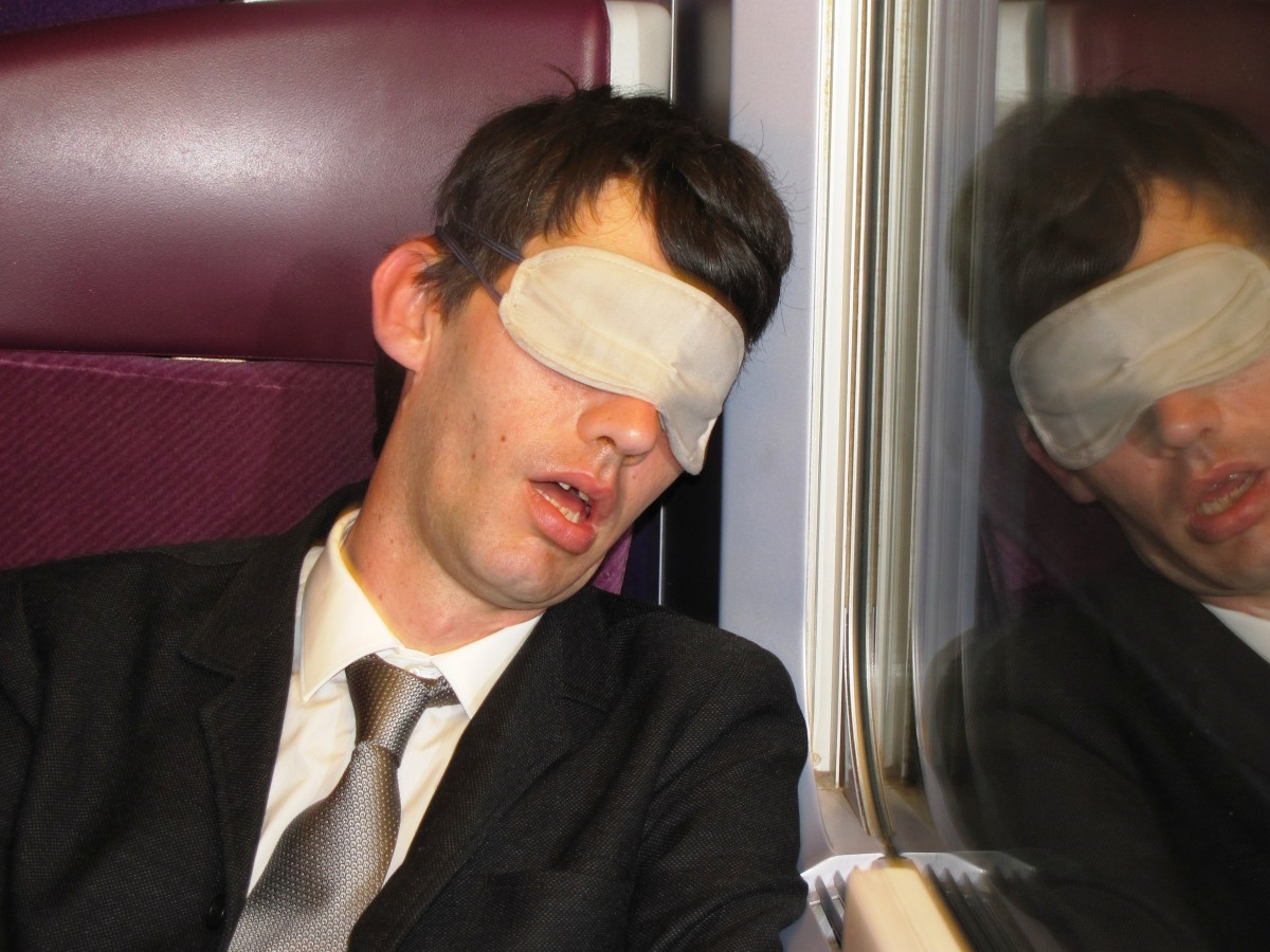 On his way to work, this weary employee tries to catch up on sleep on the train.