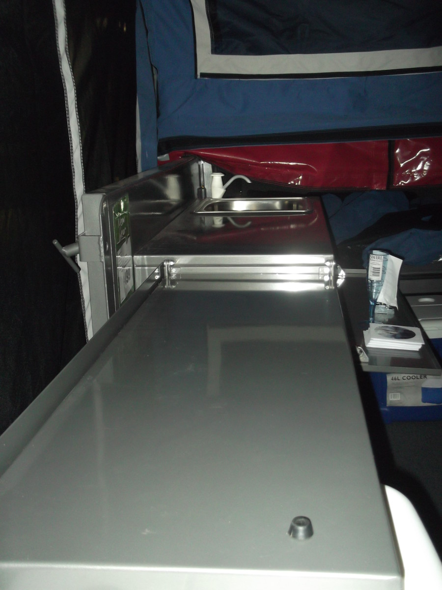 Optional kitchen sink and bench space that extends out from the rear of the trailer beneath part of the tent ... and folds into the trailer when you pack up to move.