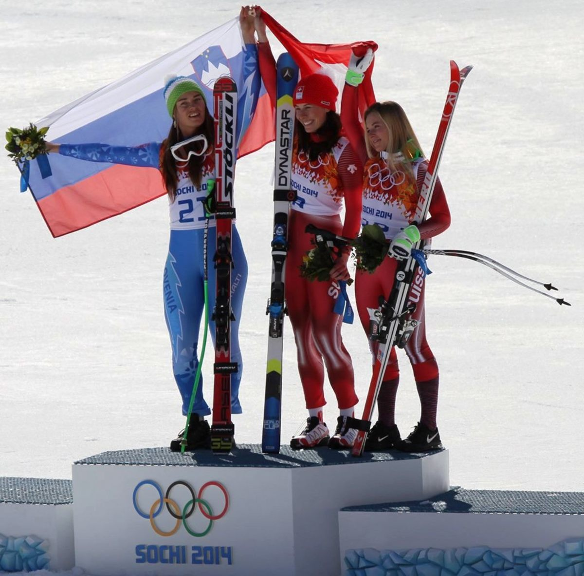 Downhill skiiers Tina Maze from Slovenia and Dominique Gisin from Switzerland tied for the Gold Medal in the 2014 Winter Olympics.  Here, they share the spotlight with Bonze medal winner Lara Gut from Switzerland.