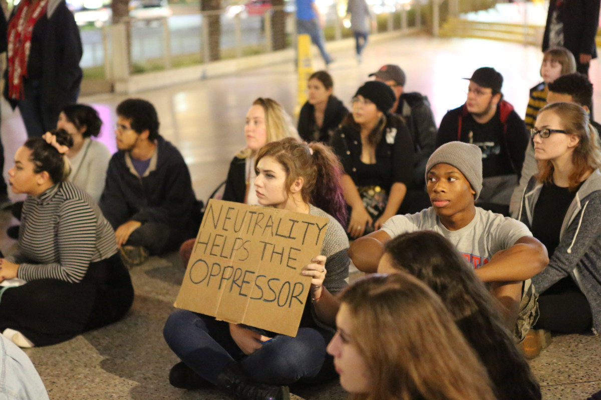"The young woman's sign references a famous quote by humanitarian and political activist Elie Wiesel: ""We must take sides.  Neutrality helps the oppressor, never the victim.  Silence encourages the tormentor, never the tormented."""