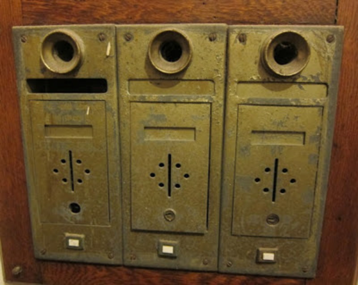 These old style apartment mailboxes, complete with speaking tubes, must have been real mailman knuckle-busters.