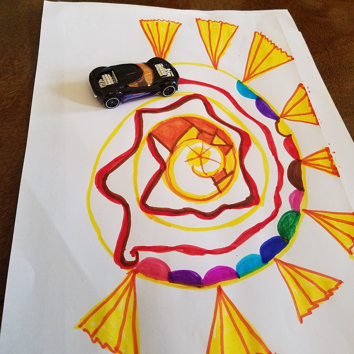 Toy car entering a spiral I drew with markers.   Play has often led to world-changing discoveries.