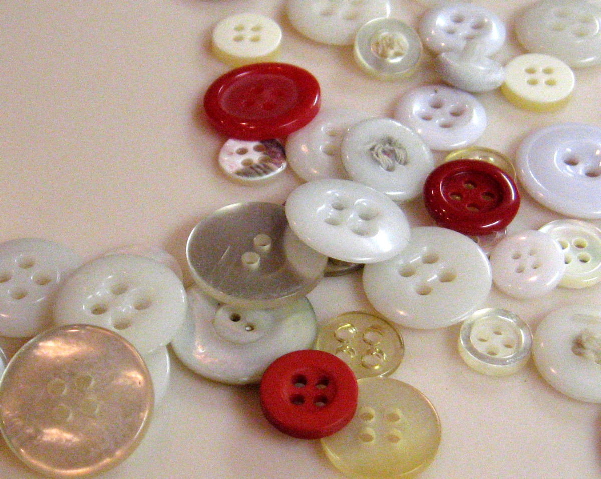 If you have a lot of buttons, sort them by color into different pill bottles. Write the color on the side of the bottle or put a label on it.