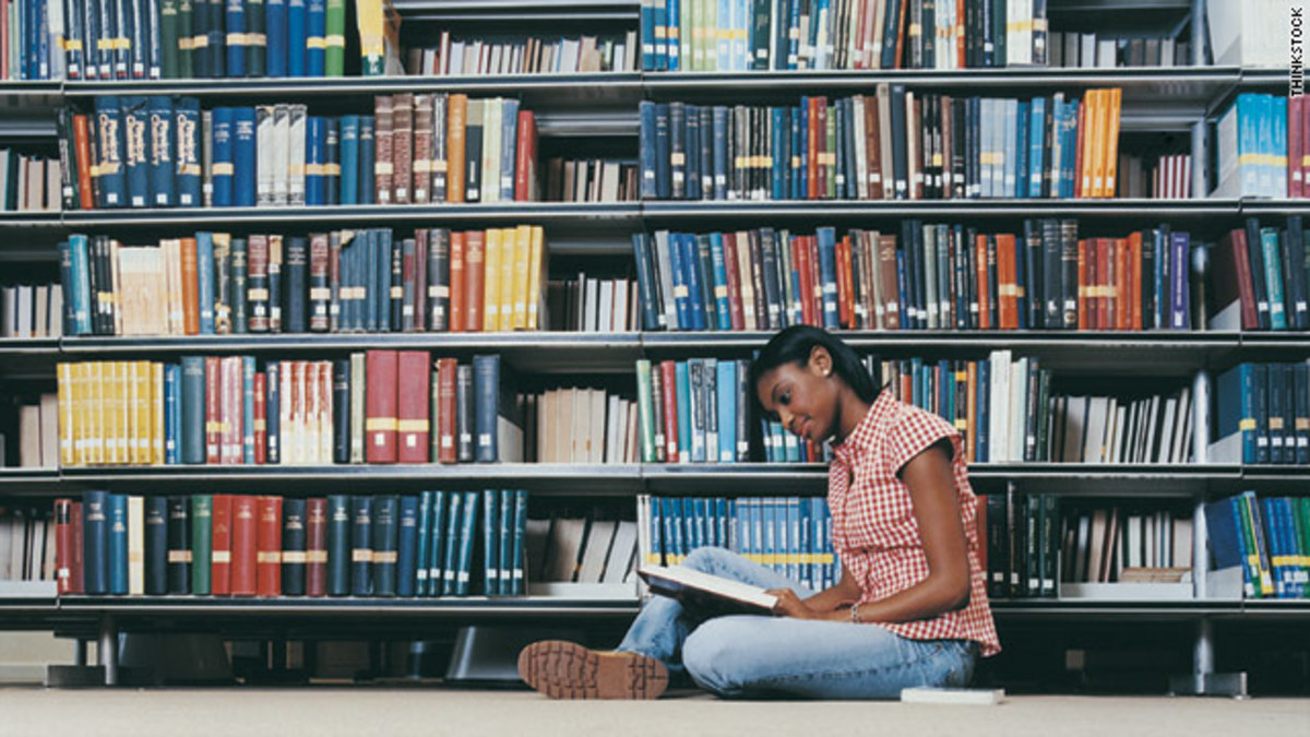 a young woman reading books at a library