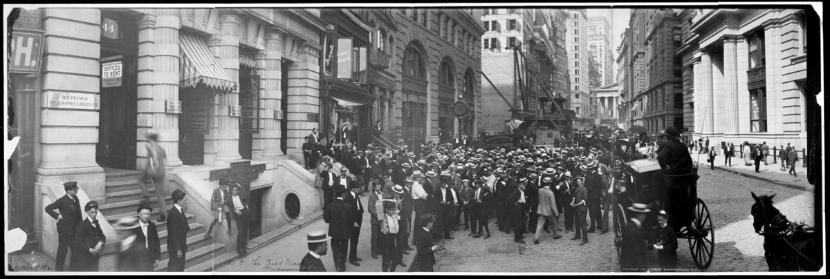 Curb market at Broad Street, in New York City. It later became the American Stock Exchange. In the background, the New York Stock Exchange building can be seen under construction.