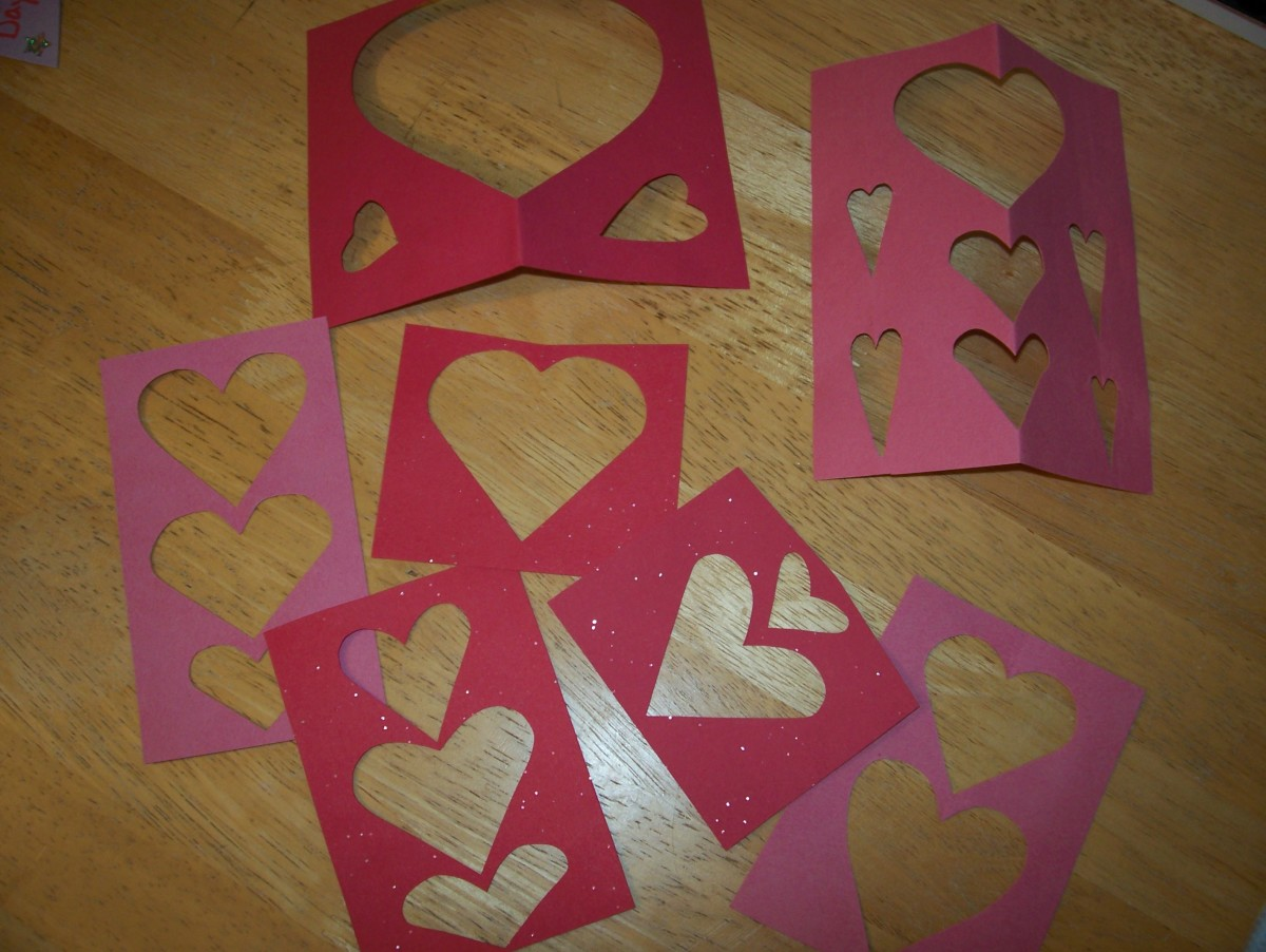Save the papers you cut the hearts out of.  You can paste them on the outsides and insides of your cards.