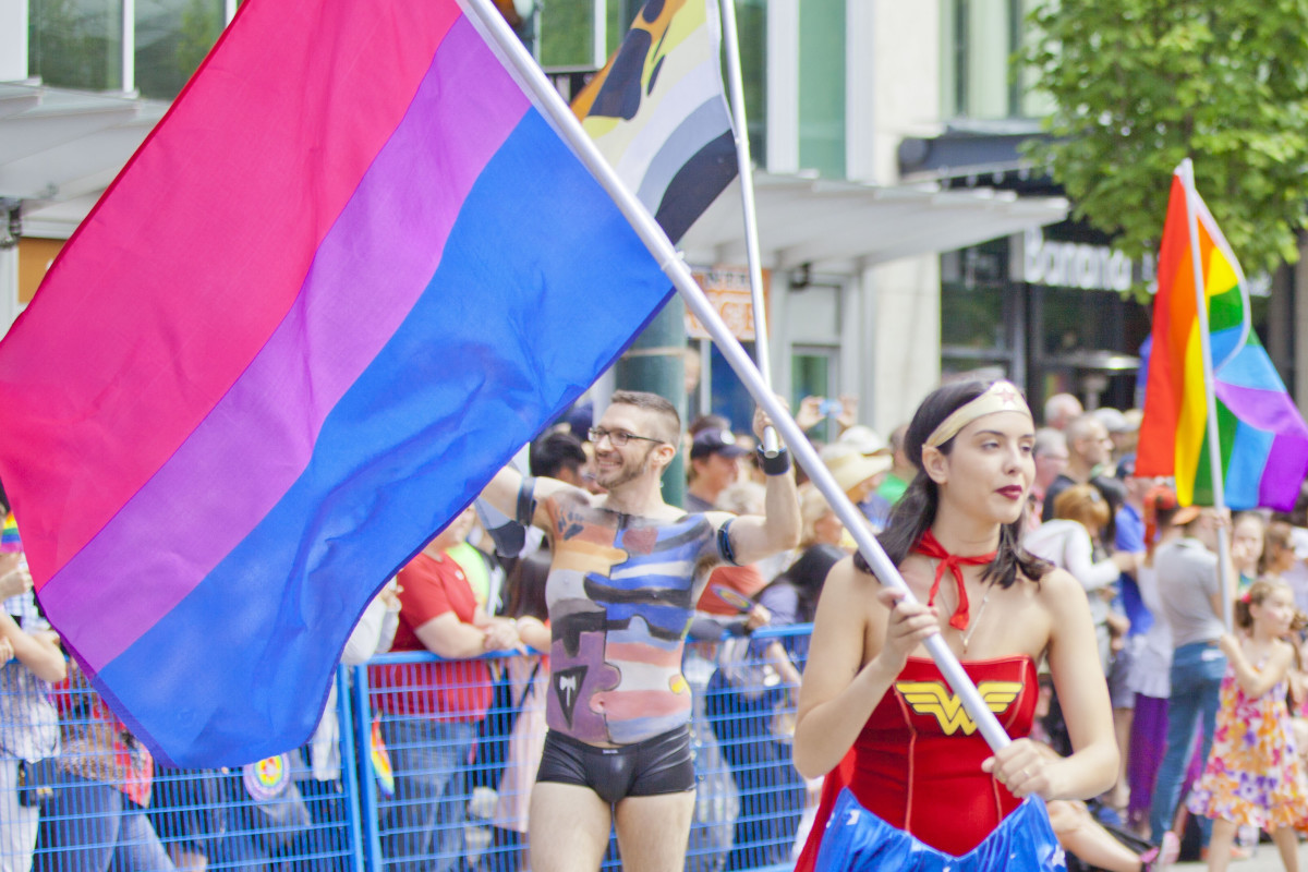 A woman dressed as Wonder Woman holding a bi pride flag at a Pride Parade
