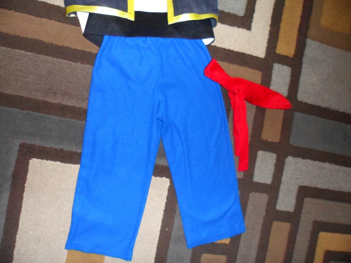 A wide black belt, blue pajama pants, and red headband complete this costume.