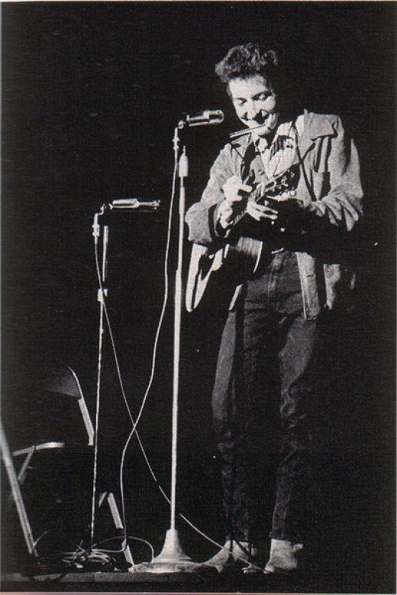 A young Bob Dylan performing at St. Lawrence University in New York.  Dylan began his career playing solo on an acoustic guitar.  It caused great controversy when he switched to an electric instrument and got a backing band in folk circles.