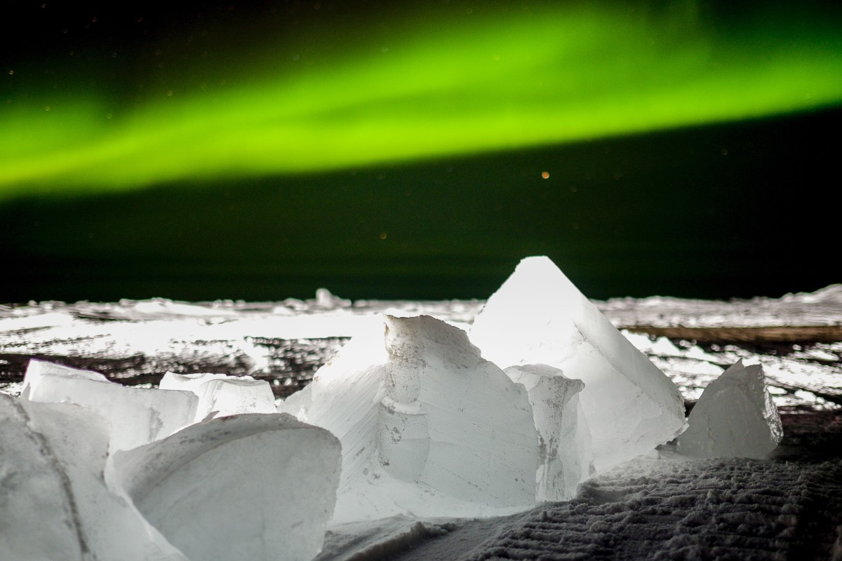 The Aurora Borealis often looks like a green curtain or drape that covers stars. It's best seen in the Arctic but is sometimes visible at lower latitudes.