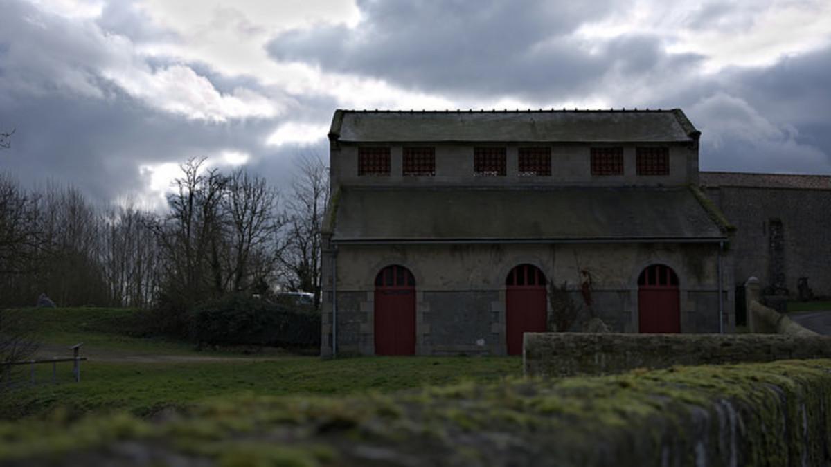 A sinister-looking slaughterhouse under a bleak sky.