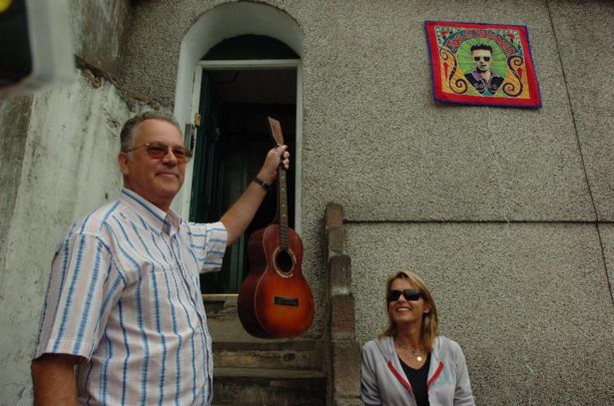 Richard Frame holding Joe Strummer's first guitar. (Joe's widow is looking on.)