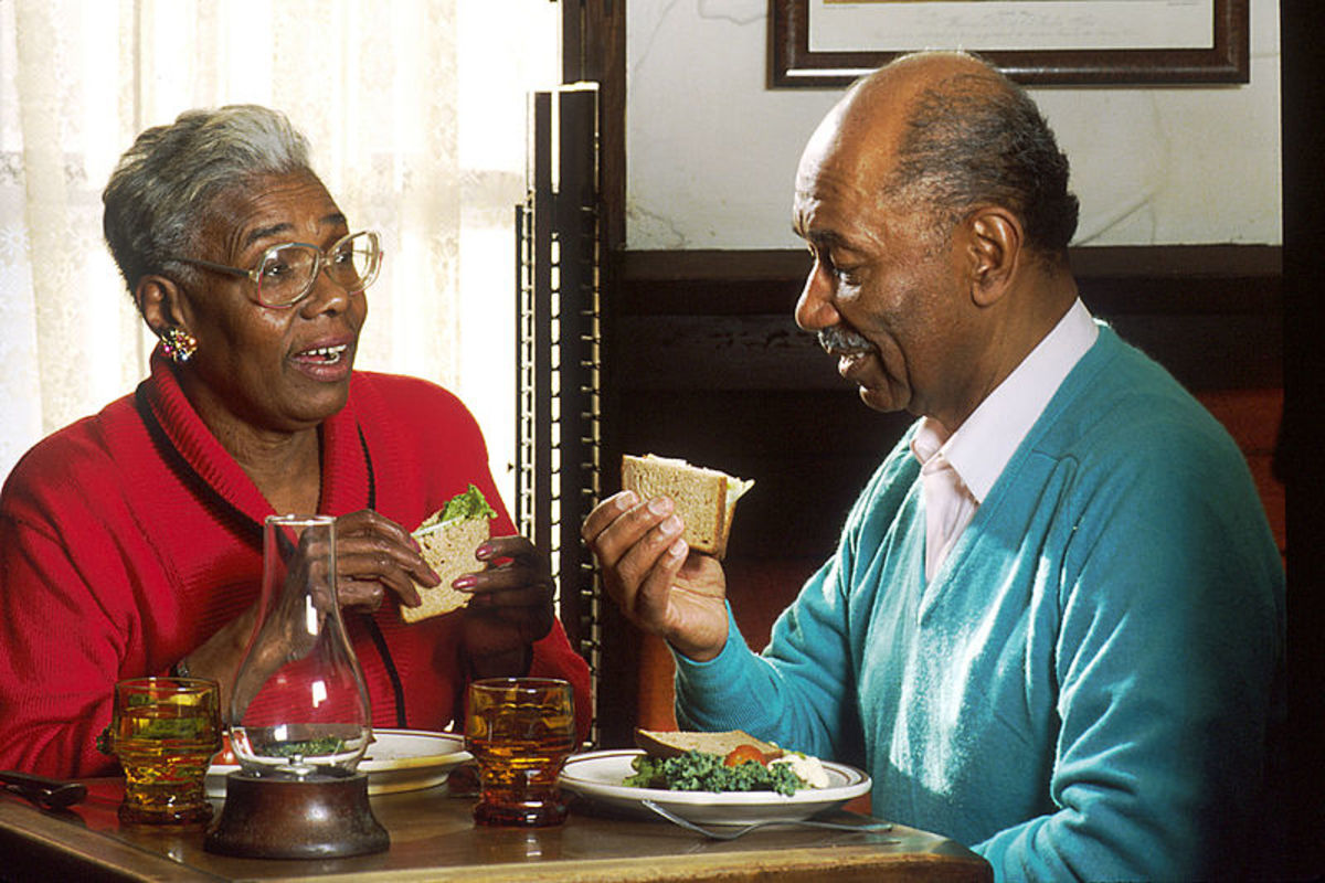 """Man and woman eating lunch at a small restaurant table"" - National Cancer Society."