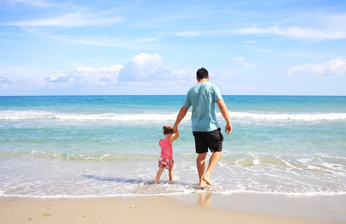 A dad with his daughter on the beach.