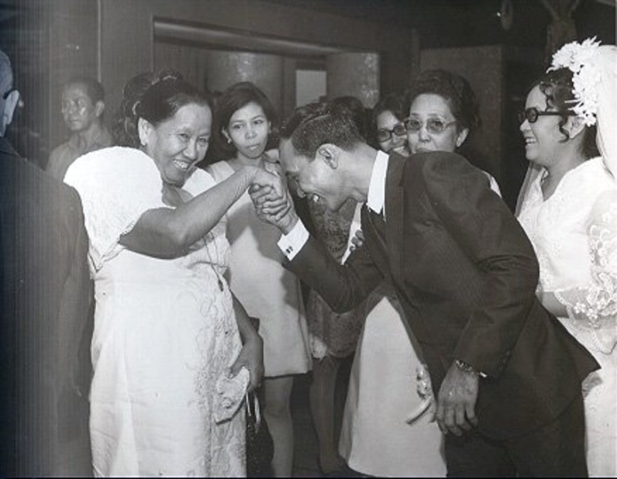 A son taking the hand of his mom and putting it to his forehead to show respect. This is an example of the Filipino tradition of mano po.
