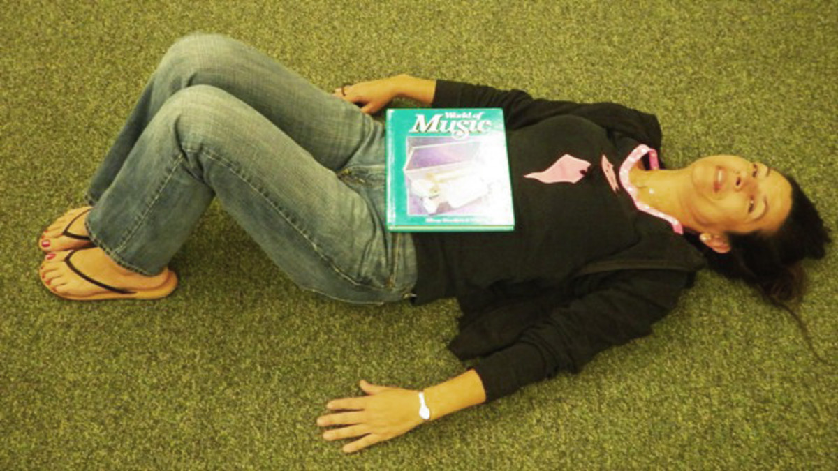 To learn to breathe using the belly breath (diaphragm), lay on the floor as pictured, book on abdomen centered at the waistline.  As you inhale, expand the abdomen and lower ribcage which will lift the book.