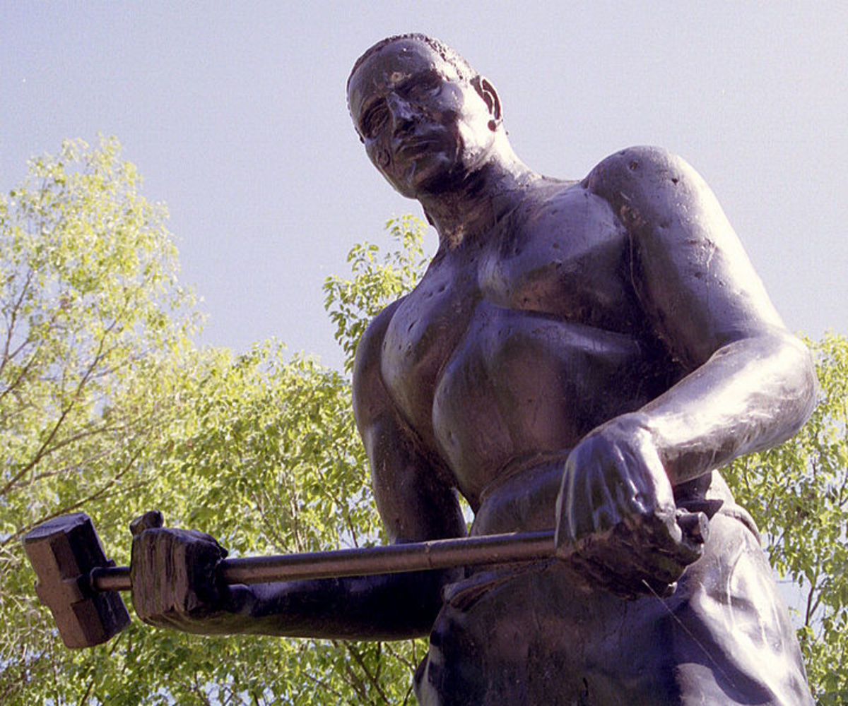 John Henry statue, near Big Bend Tunnel, WV; his story is told in the folk song heard below. Image courtesy Ken Thomas and Wikimedia Commons.
