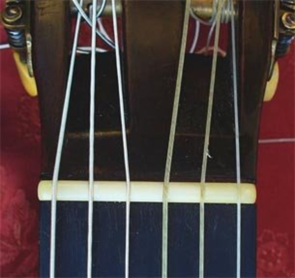 The nut. It doesn't look like a nut, but it plays an important role in the placement of your strings. It is the horizontal white bar, just below your headstock.