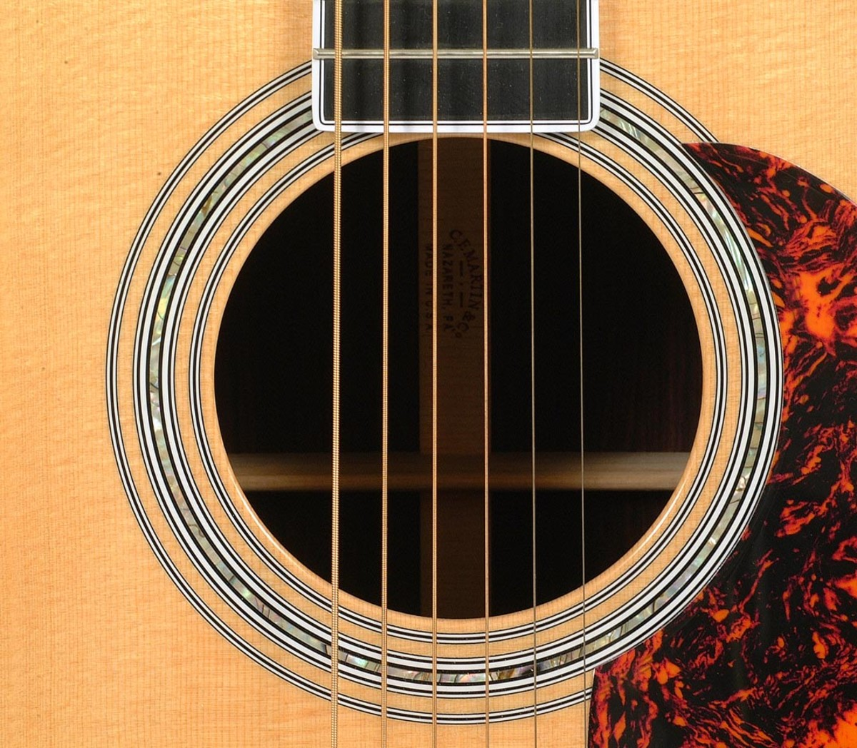 The soundhole is where the acoustics happen. It's best to play just over the soundhole on the guitar, for maximum sound.