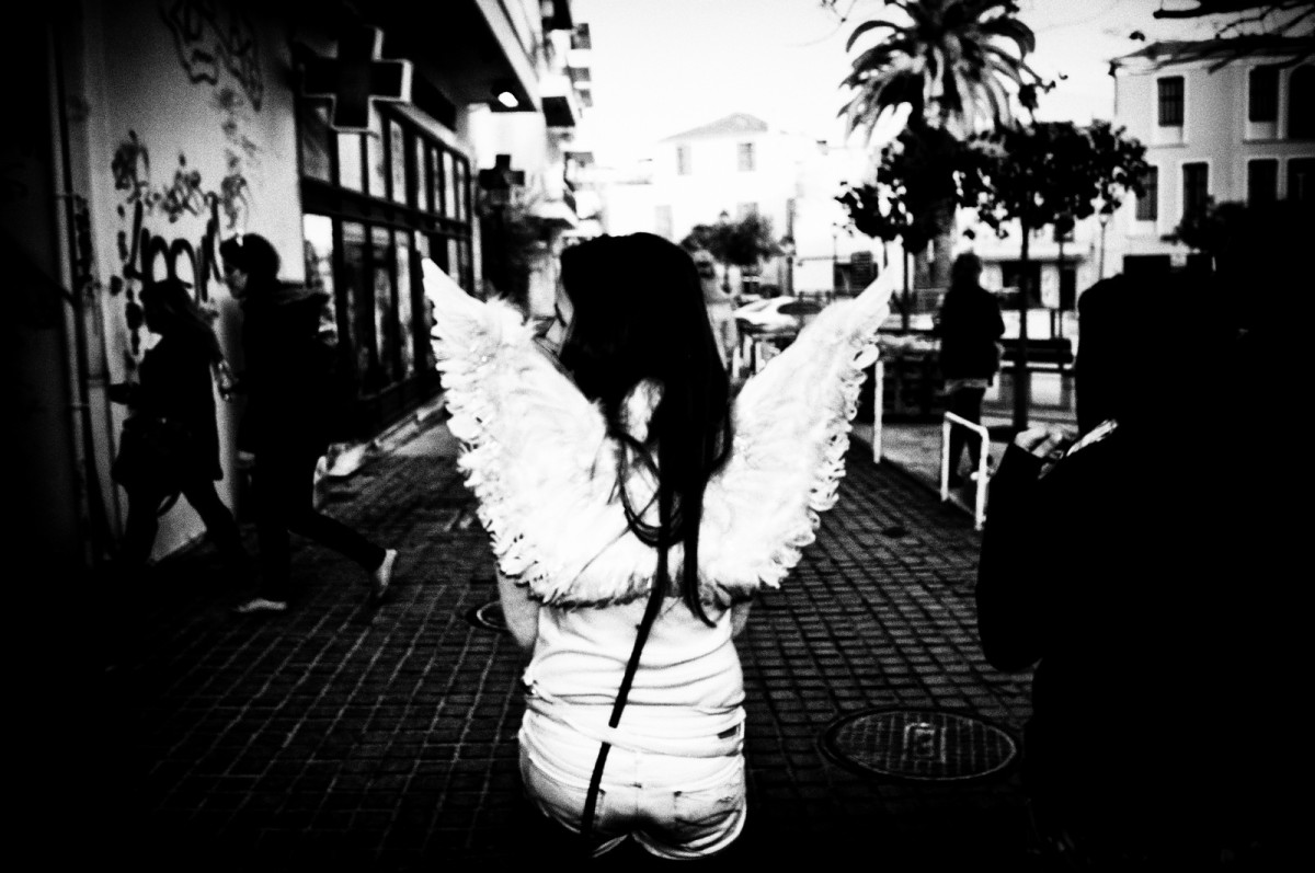 This everyday angel combs the boulevard during a festival, looking lost.