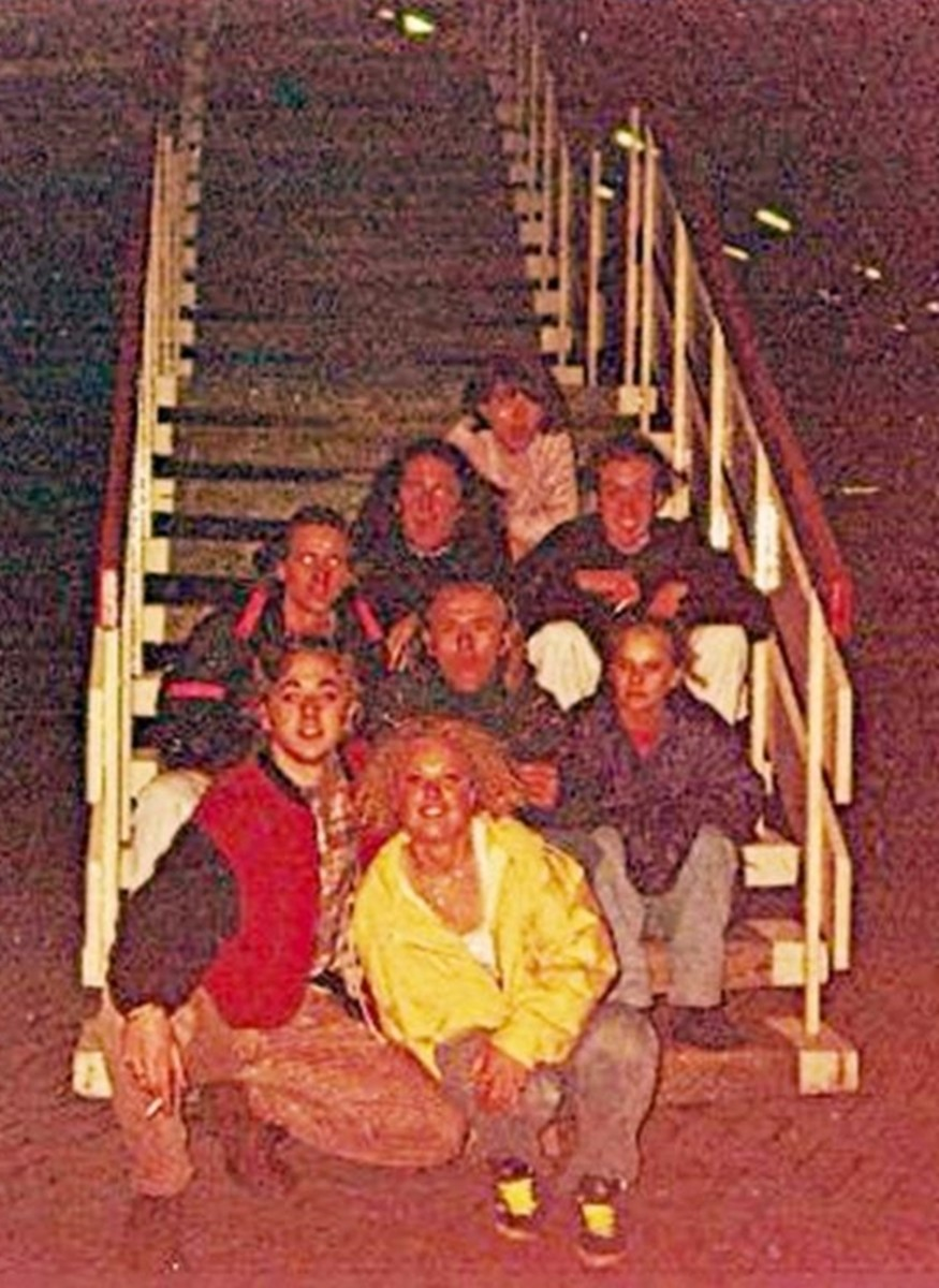Sitting on the motorway services (1991). My friend Carol is right at the back. On the step in front of her are Zoe (on the left) and Glyn. Right at the front, in the yellow jacket, is Jane.