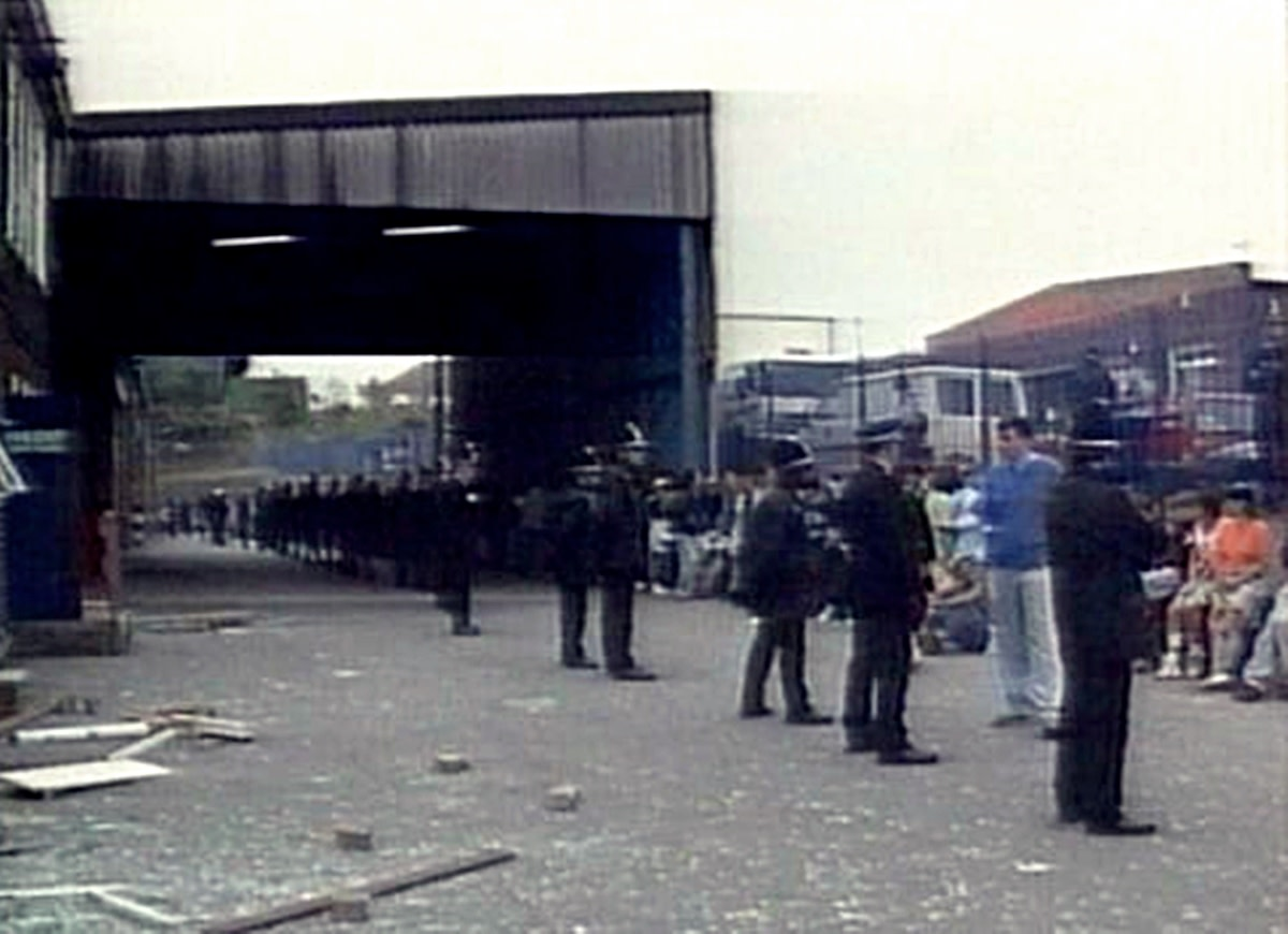 The police line up in front of clubbers after stopping an illegal rave.