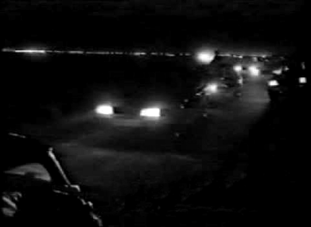 The familiar sight of car headlights on the motorway as a convoy of ravers make their way to a party (1989).