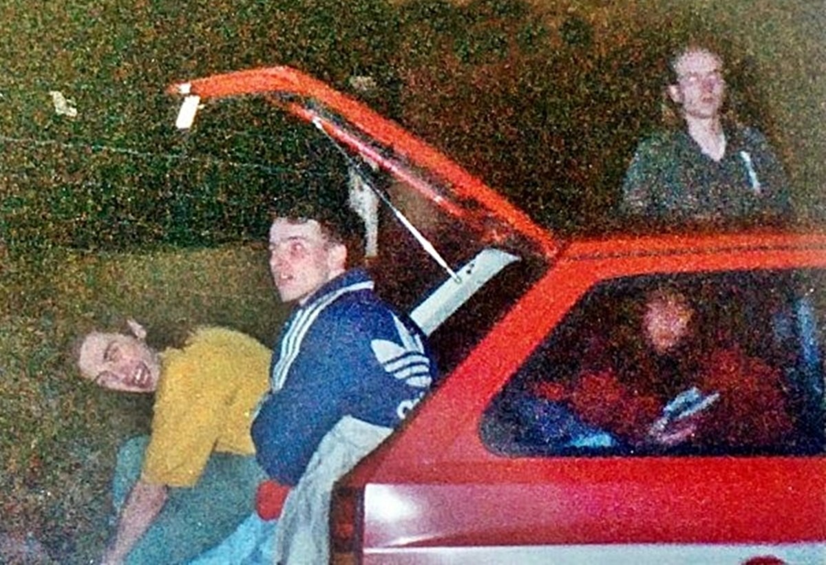 My friend Bollie (in the yellow t-shirt) getting changed in the back of a car outside Monroes (1991).