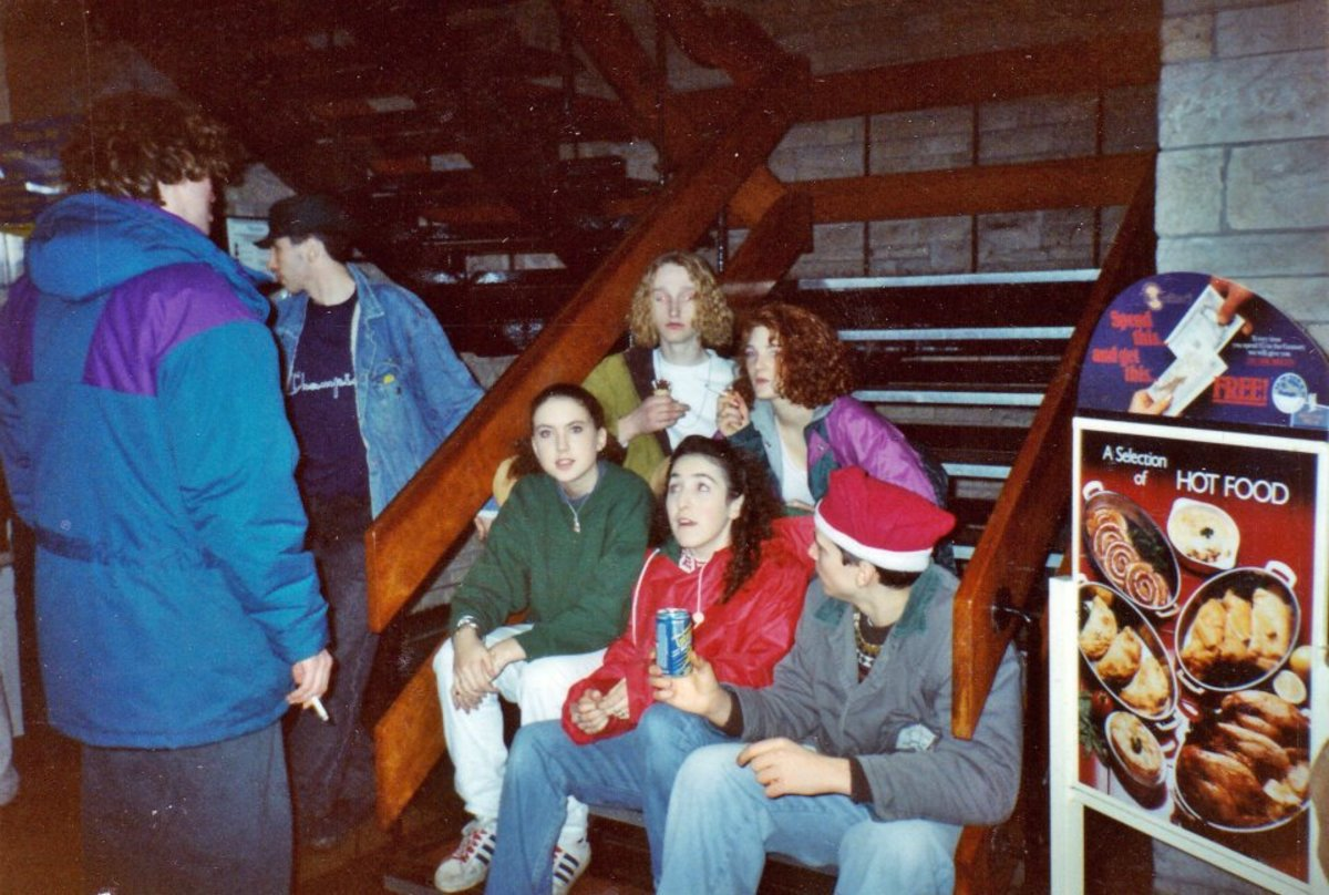 Motorway services after Monroes (1990). My friend Kat is sitting at the back, on the right. Cushla is at the front on the left and next to her, Nyree, in the red jacket.