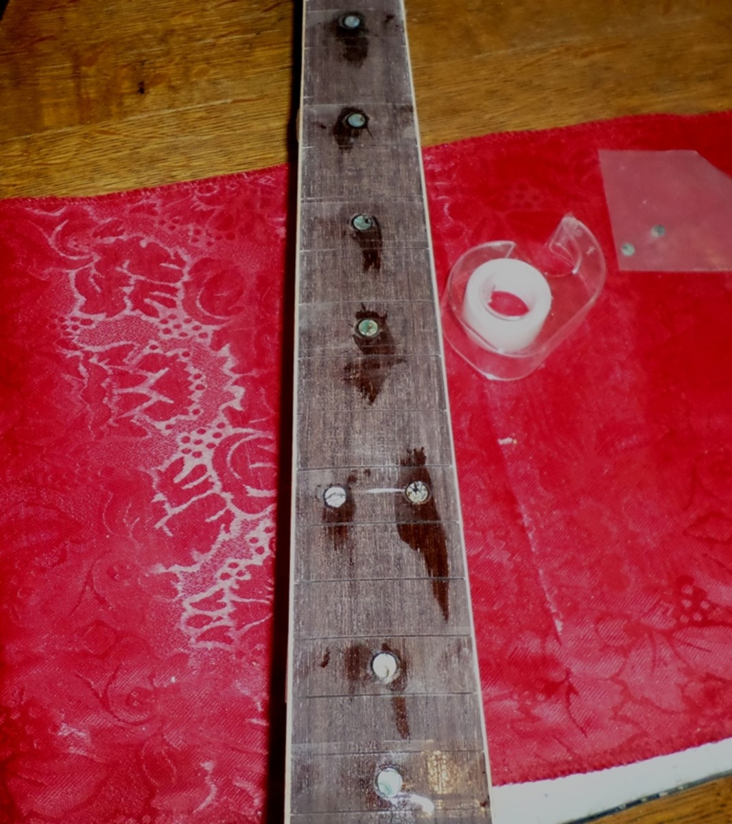Gluing the fret dots in place.