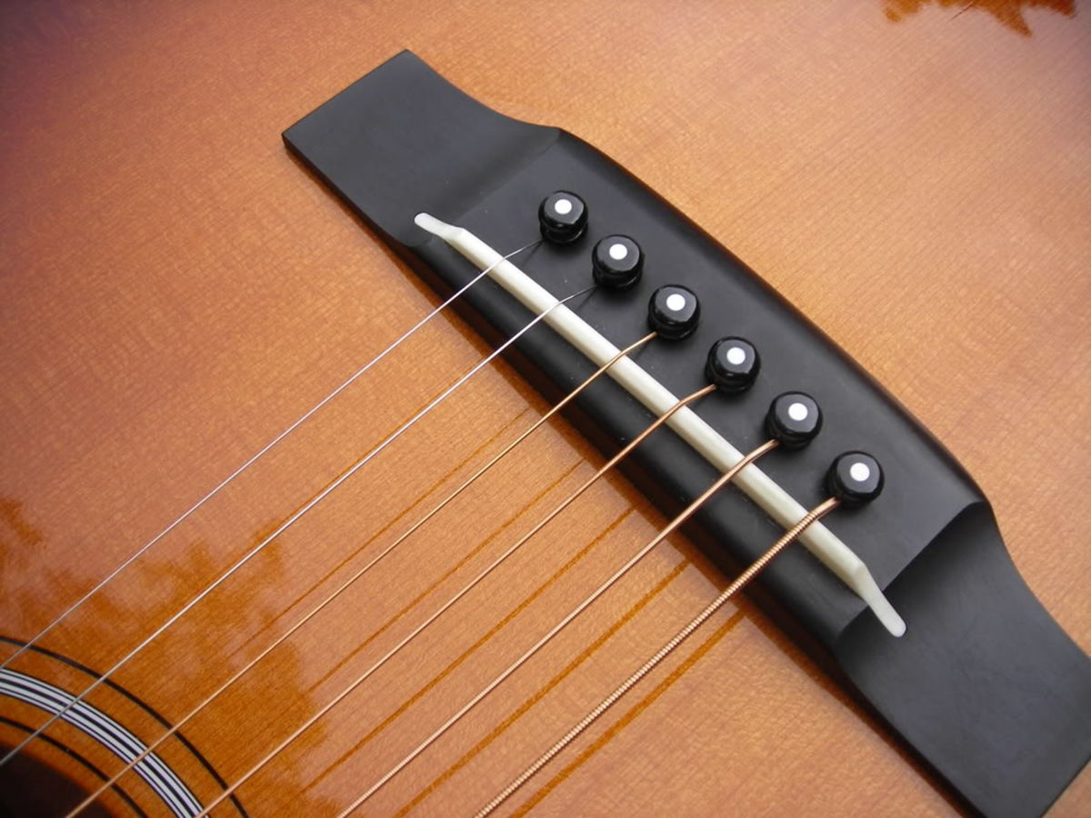 An acoustic bridge with saddle and pins.