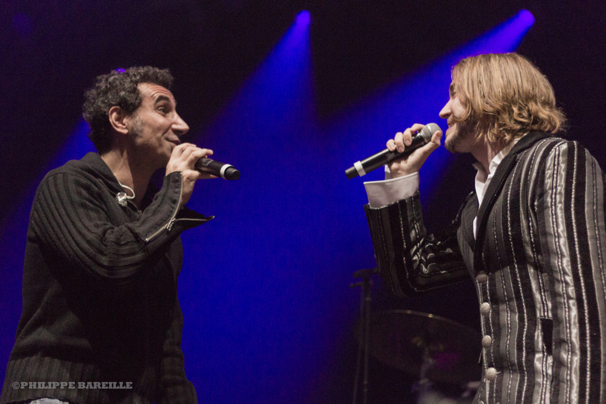 Serj Tankian (left) performing with Viza's K'Noup Tomopoulos (right) at Le Zénith de Paris in 2012