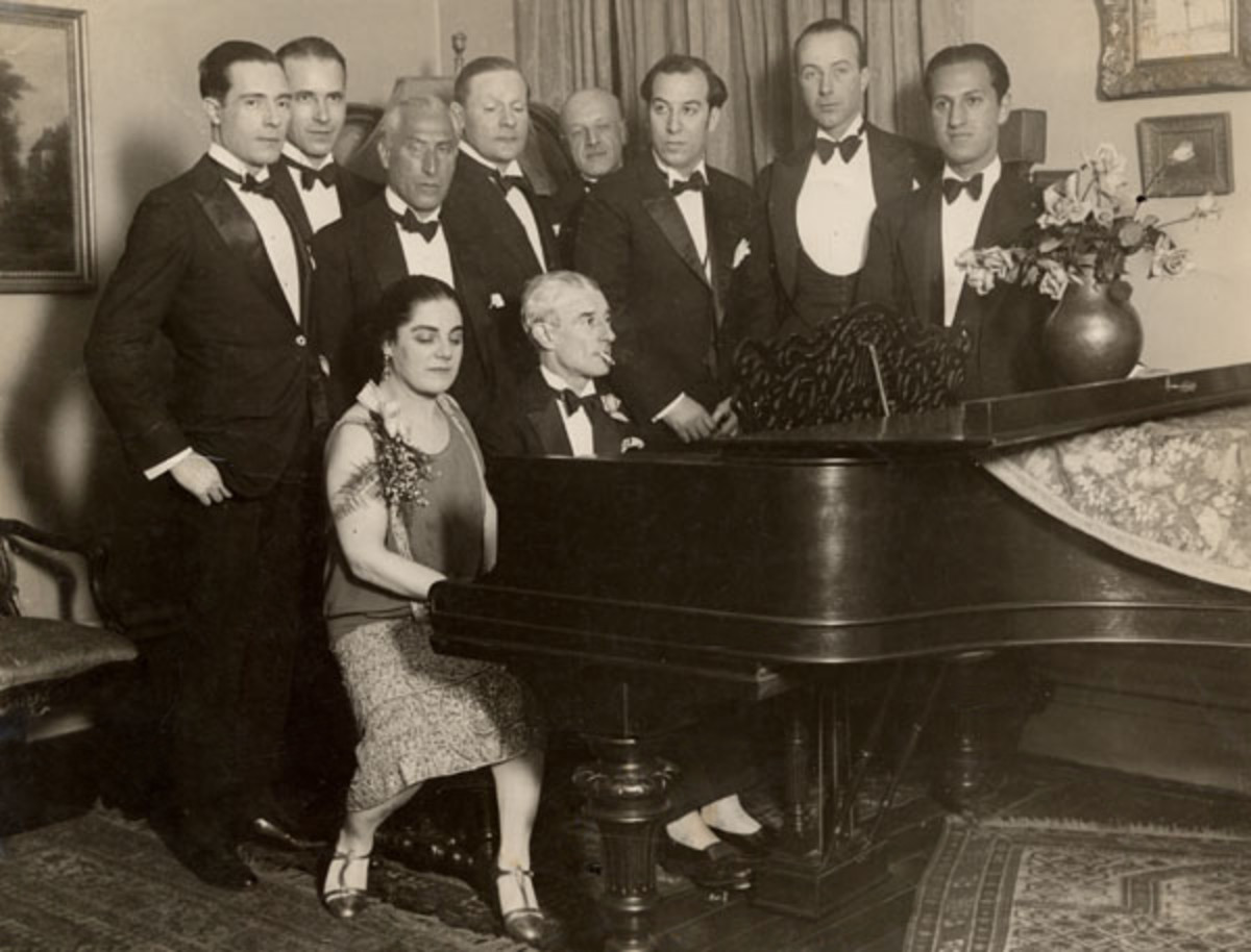 Maurice Ravel 1875-1937. The photo was taken at an evening soiree at the home of Eva Gauthier given in honour of  Ravel's birthday in 1928.  Ravel is seated at the piano. George Gershwin is one of the guests arranged around it, on the extreme right.