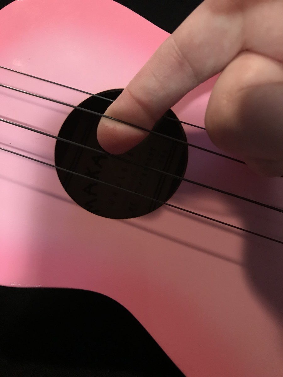 Stretching the new strings on a soprano ukulele.