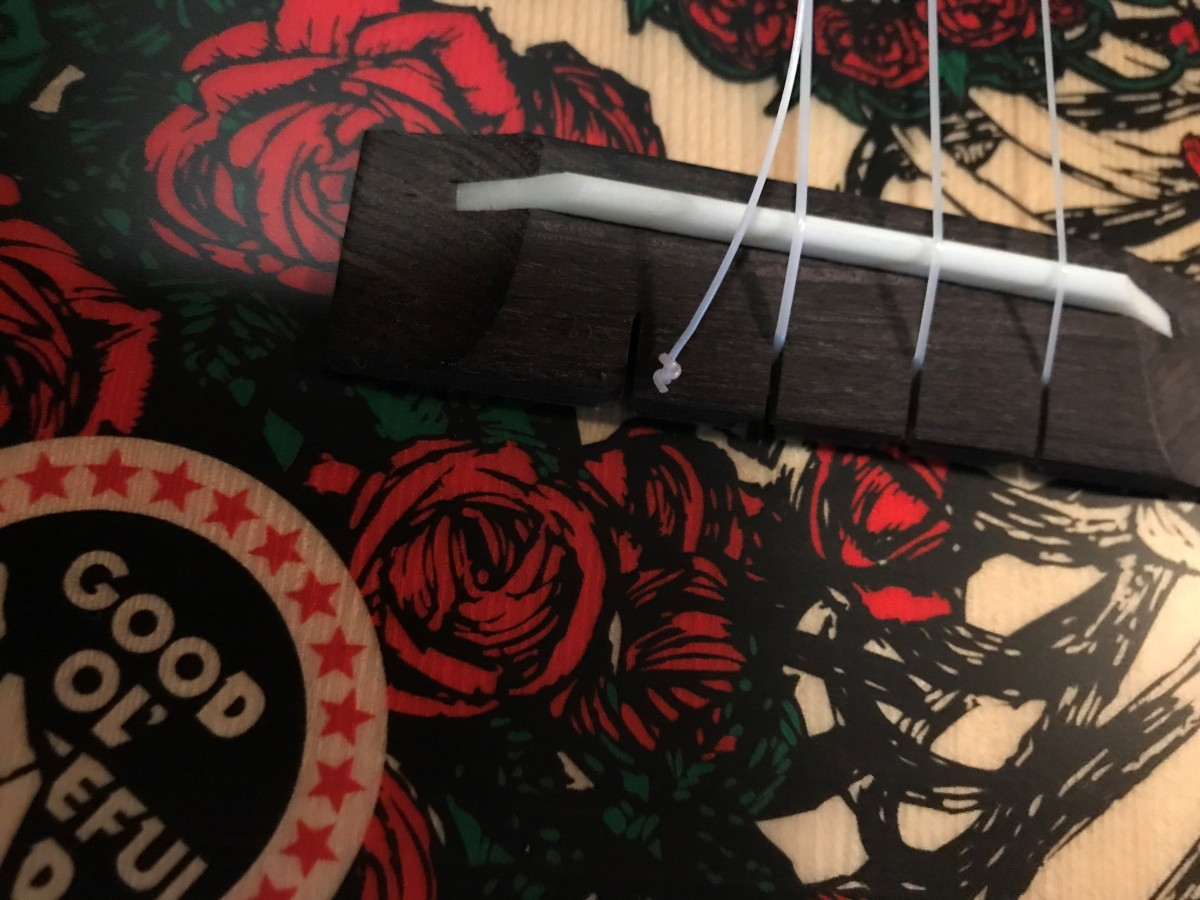 Removing old strings from ukulele with a standard bridge.