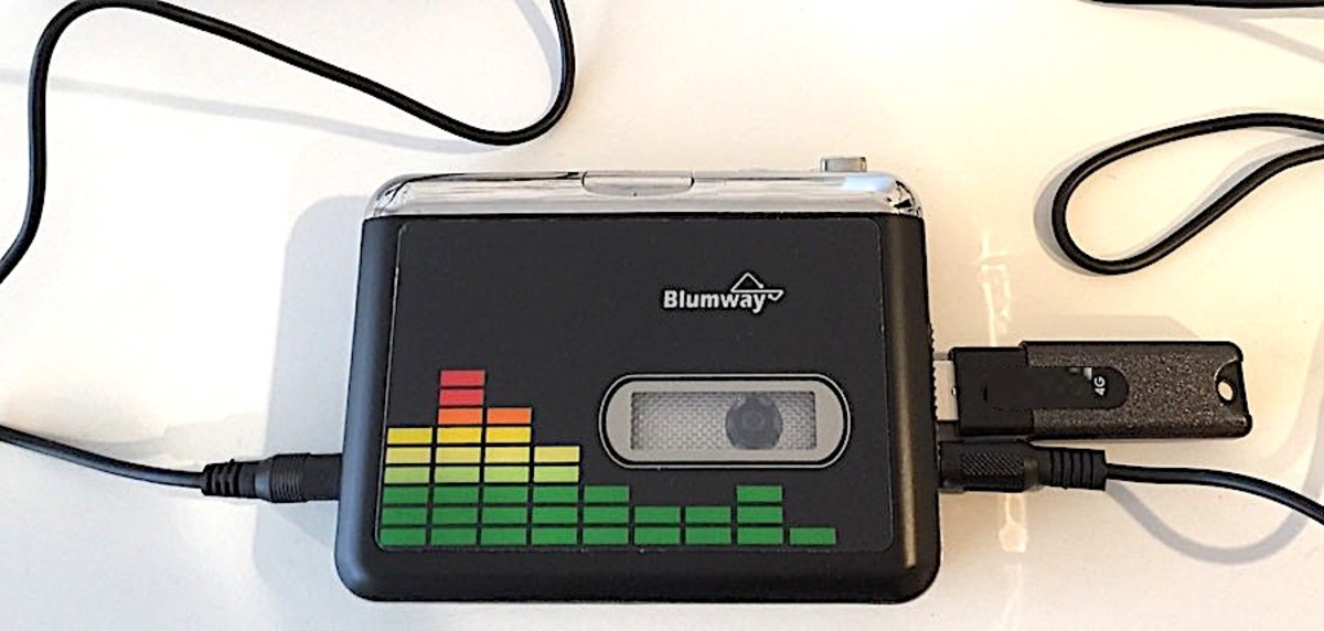 BlumWay with earbuds and flash drive connected on the right and USB power connected on the left.