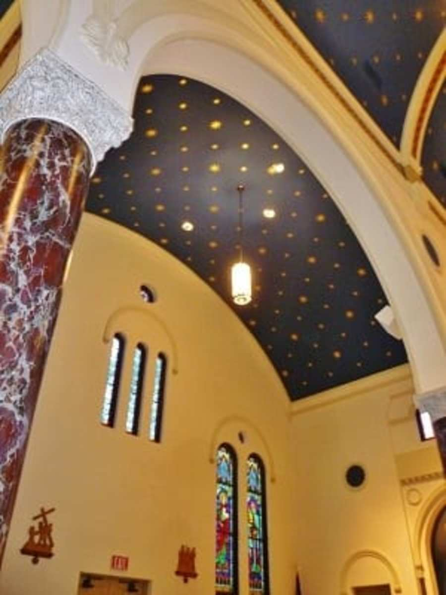 Partial view of arches, ceiling, and stained-glass windows