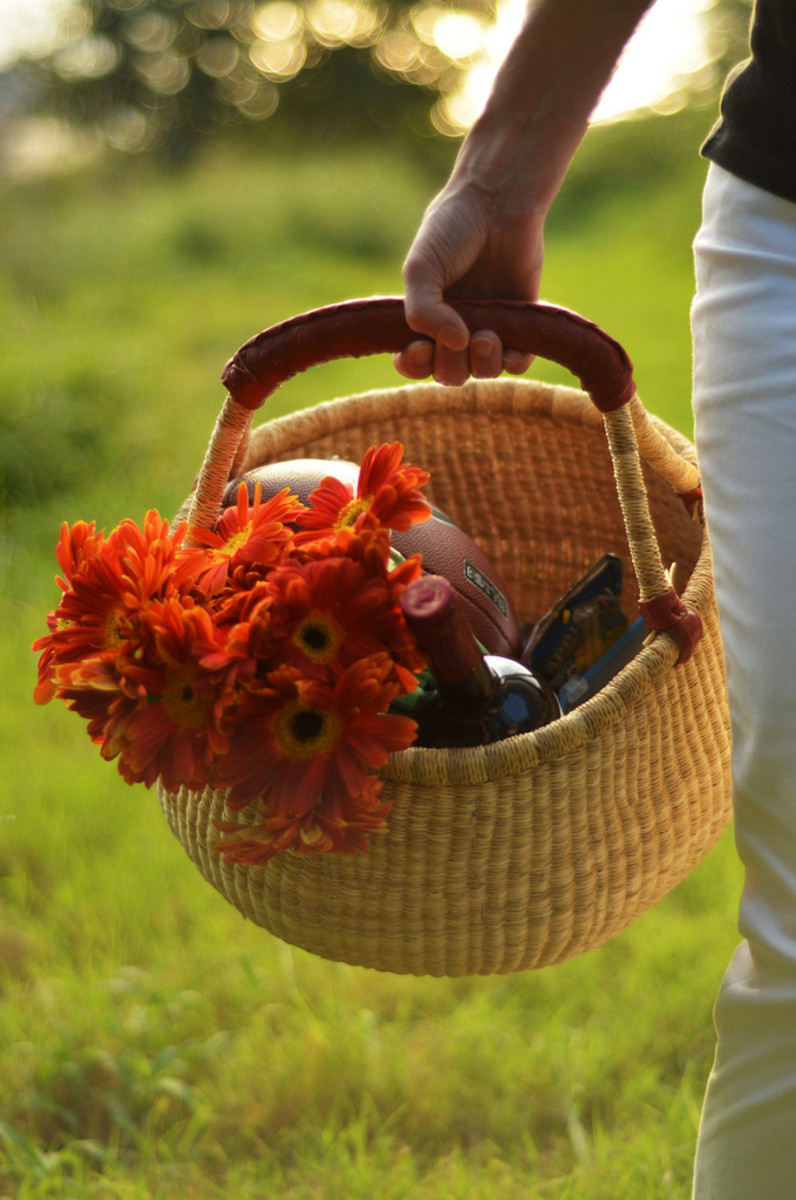 Picnic basket filled with flowers, wine and activity.