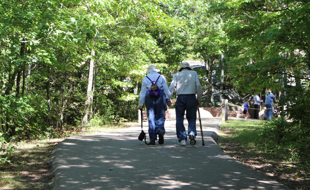 A couple takes a walk together, giving each other company and loving support.