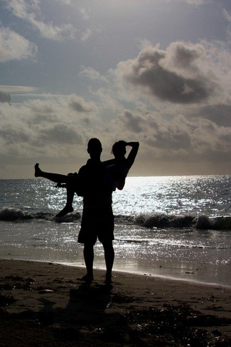 A couple frolics by the ocean as they share a life of bliss together.