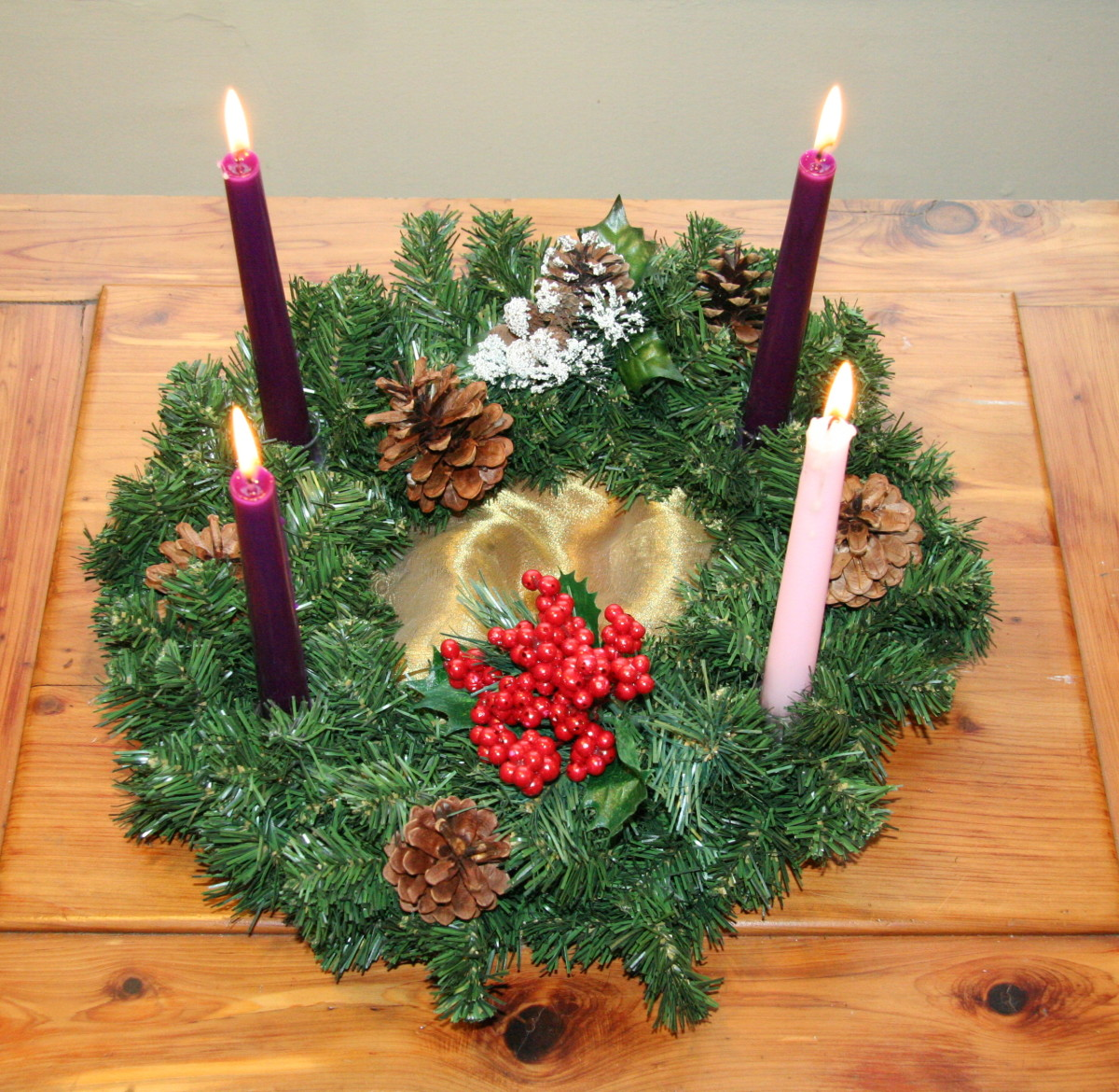 An advent wreath in the traditional Catholic colors. Most of Advent is purple for penitence, with a break in the third week for the rose light of joy.