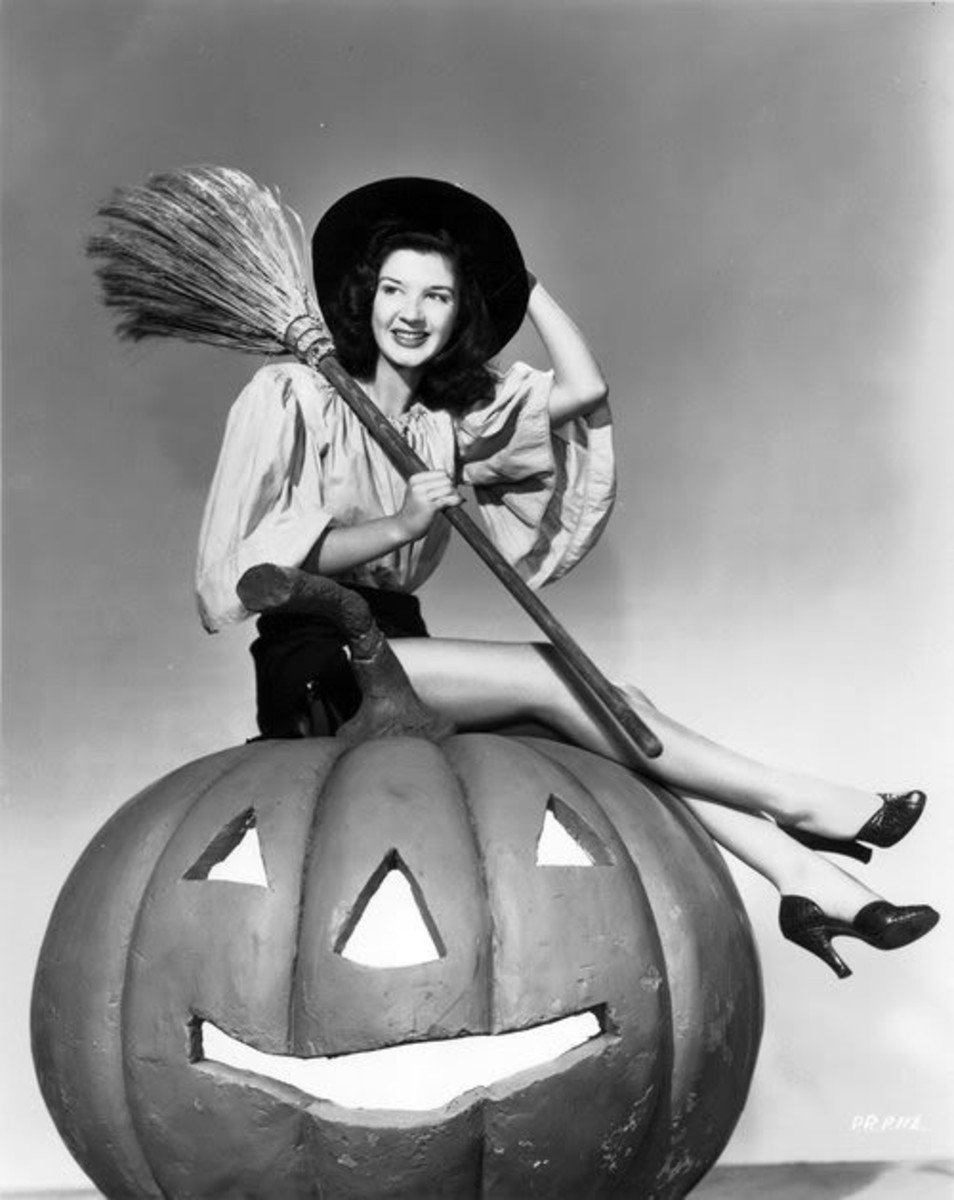 Joanna Pettet poses on top of a gigantic pumpkin as a beautiful witch
