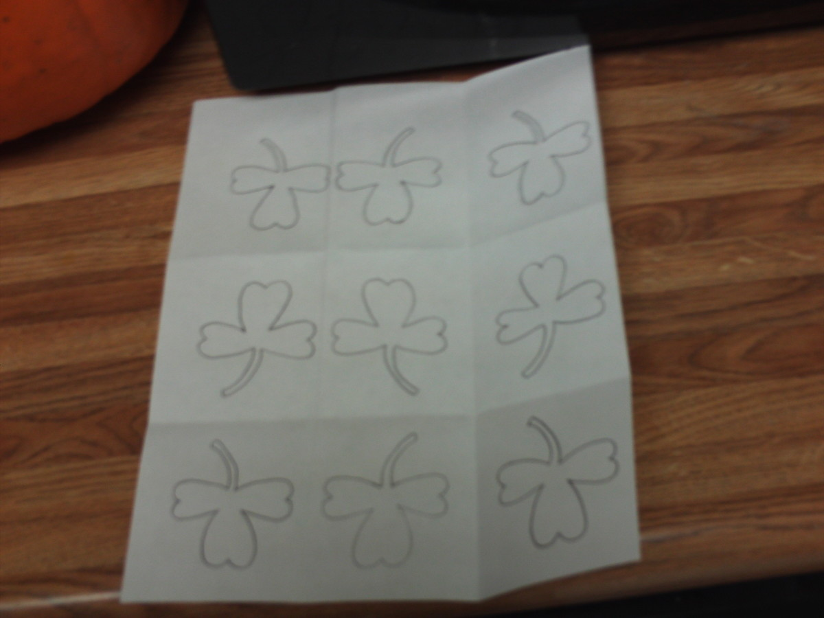 Fold the paper into several sections to draw and trace baby shamrocks.