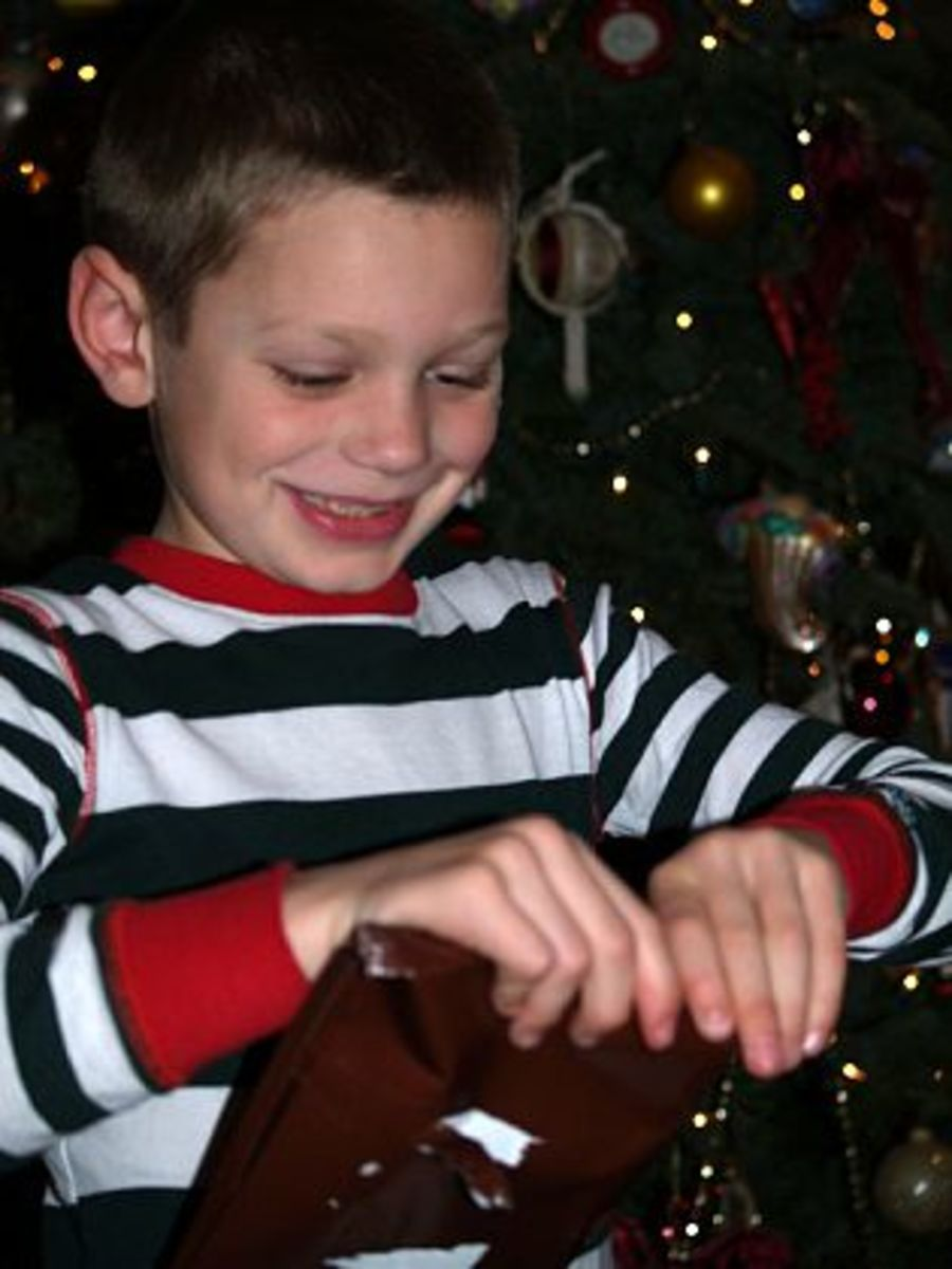 Joy in the face of a young boy opening presents