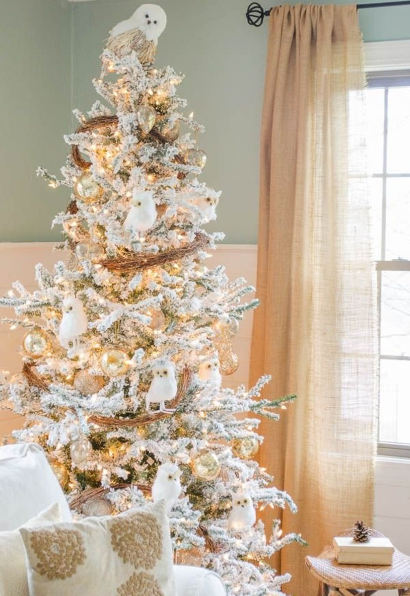 flocked christmas tree decorated with snowy owls