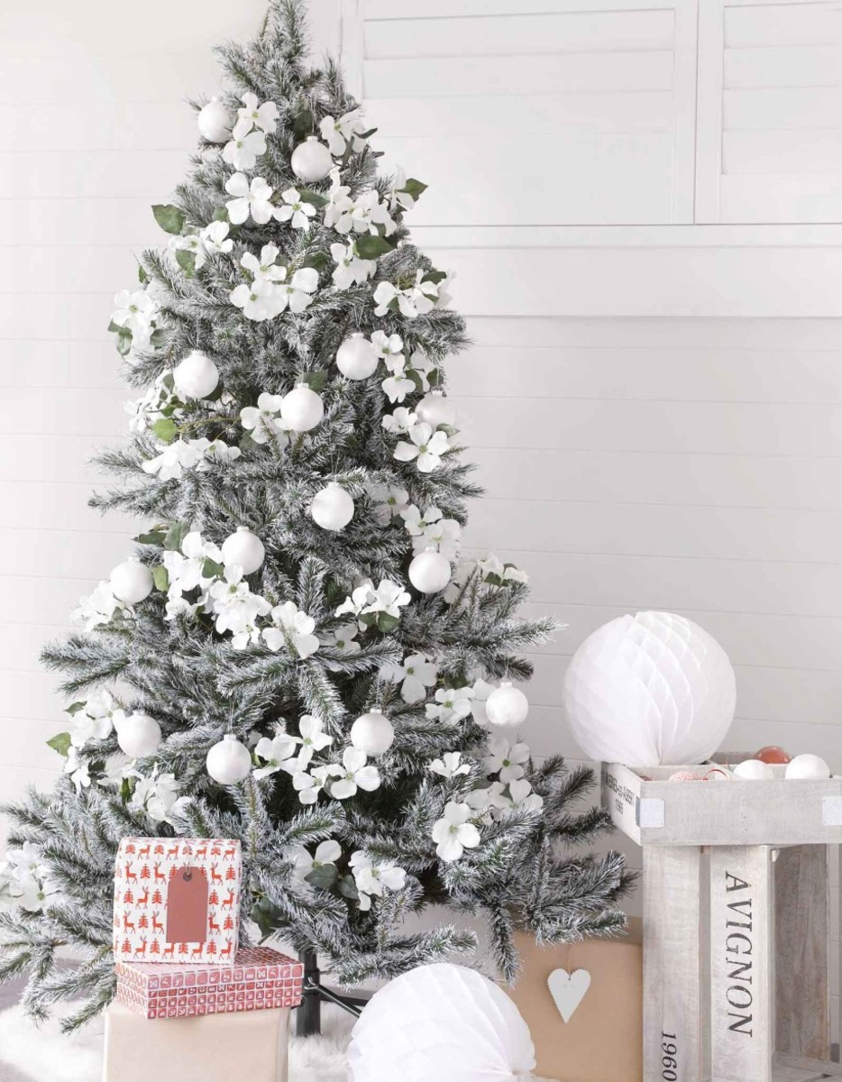 Christmas tree decorated with white faux flowers.