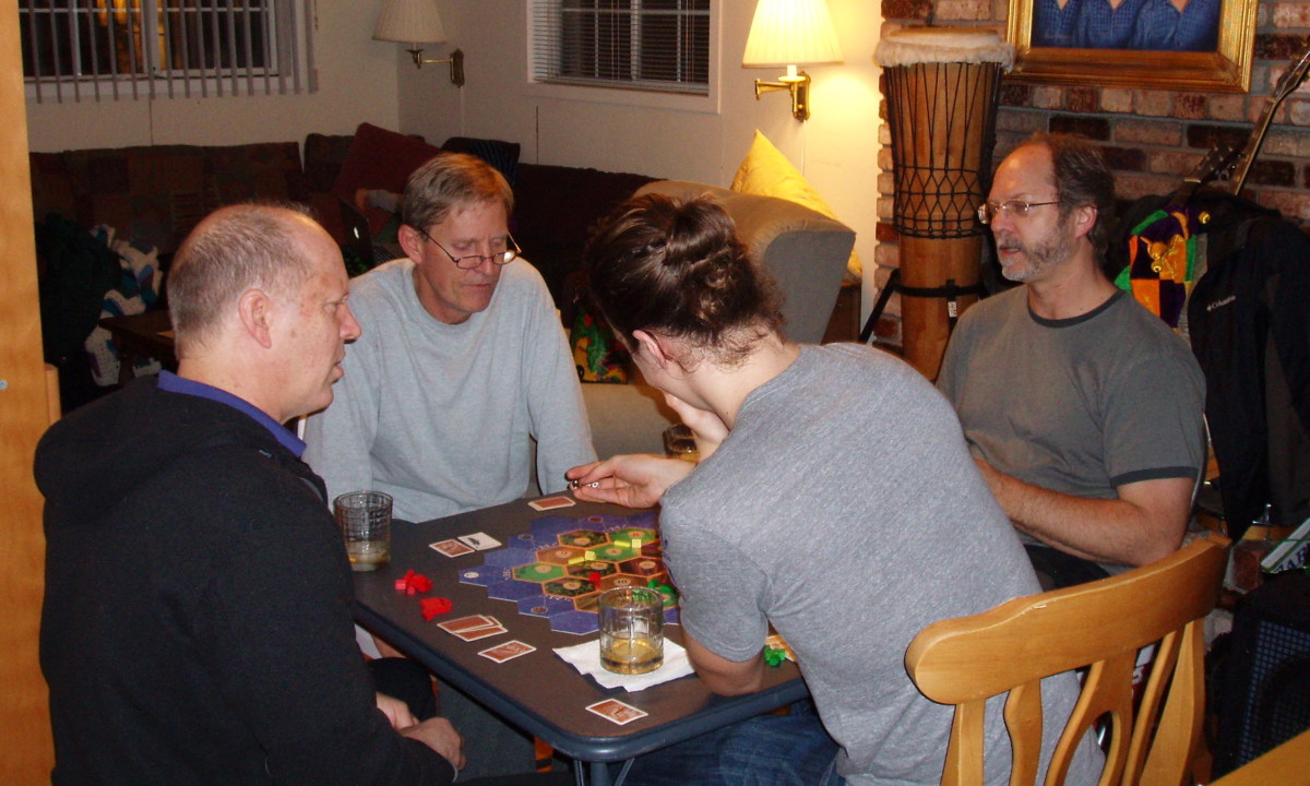 Three brothers and a nephew playing Settlers of Catan. Originally a German game, it won game of the year the same year my now-deceased brother introduced it to us in 1995.
